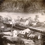 A train filled with Union soldiers bound for the front lines of the war c.1864 sits on the tracks of the Winchester and Potomac Railroad in Harpers Ferry (Bowlsby, photographer; United States Military Academy, West Point)