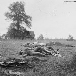 The photographers wagon sits in the background of this photograph of dead Confederate soldiers near the Emmitsburg Road (July 5, 1863, Alexander Gardner, photographer; Library of Congress)