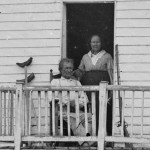 Detail of the previous image showing Burns and probably his wife on the porch of their house