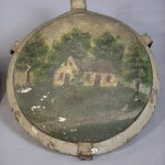 Civil War metal canteen, featuring oil paintings of the Dunker Church on one side and the Burnside Bridge on the other. This canteen was donated by Elmer Boyer, a local man who salvaged the wreckage of the Dunker Church when it collapsed in a windstorm in 1924, and preserved the materials until it was reconstructed in 1962. (Antietam National Battlefield)